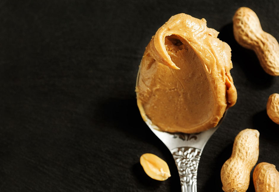 47935494 - peanut butter in spoon over black background